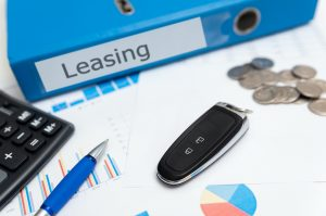 Car keys, remote control, binder with leasing label. Car leasing concept