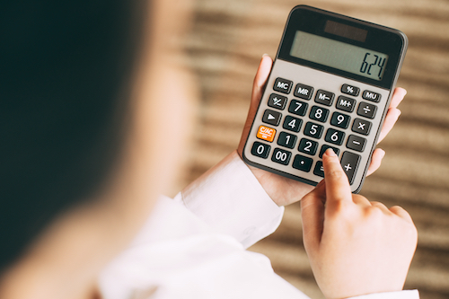 Young businesswoman using calculator in office. Young woman counting her home budget