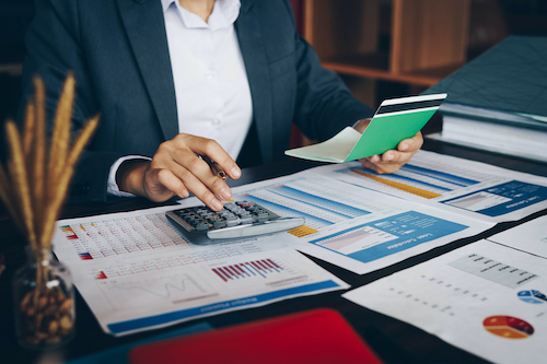 Businesswoman on desk in office using calculator to calculate saving account passbook and statement with financial report .Female accountant or banker use calculator. Savings, finances and economy concept.